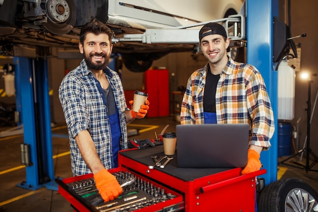 Portret dwóch uśmiechniętych specjalistów pracujących na laptopie i patrzących na front w nowoczesnym centrum serwisowym