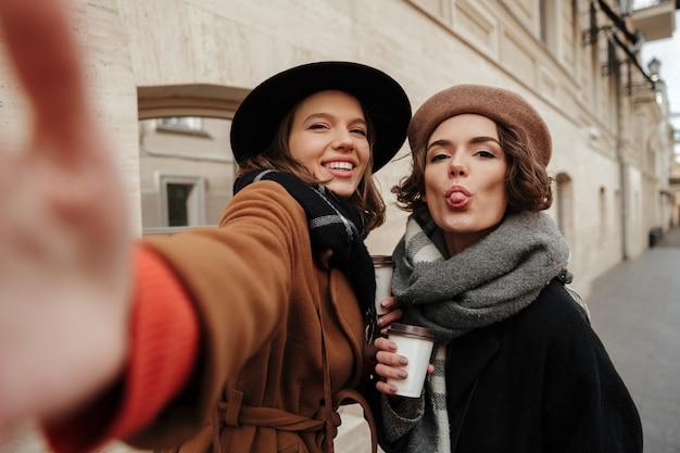 Portret dwóch wesołych dziewcząt ubranych w ubrania jesienne