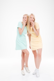 Portret dwóch wesołych dziewczyn śmiejących się na białym tle nad białą ścianą