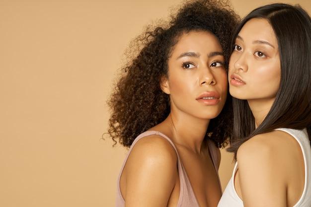 Portret dwóch wspaniałych młodych kobiet rasy mieszanej z idealną skórą, odwracającą wzrok podczas pozowania