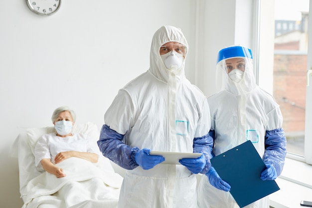 Portret dwóch współczesnych lekarzy stojących razem na oddziale szpitalnym z pacjentem za nimi