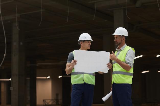 Portret dwóch wykonawców budowlanych omawiających plany stojąc na placu budowy przemysłowej,