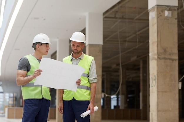 Portret dwóch wykonawców budowlanych omawiających plany stojąc na placu budowy,