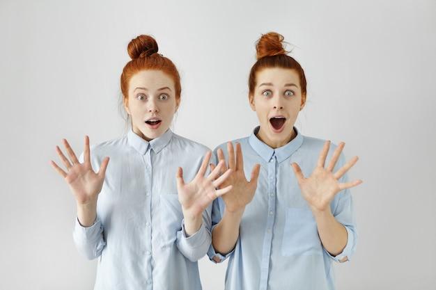 Portret dwóch zaskoczonych rudowłosych dziewcząt z kokami, ubranych w podobne ubrania