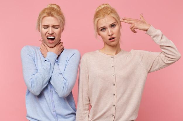 Portret dwóch zmęczonych pięknych młodych bliźniaków blondynka próbujących się zabić, na białym tle na różowym tle.