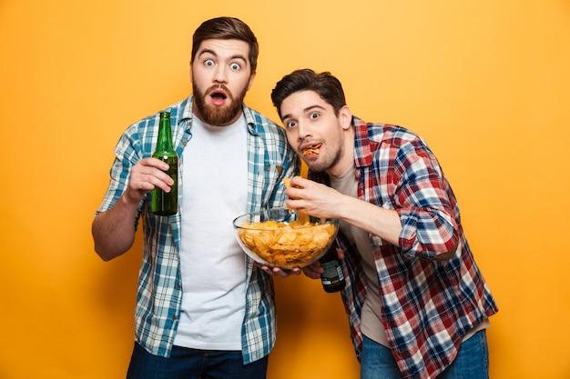 Portret dwóch zszokowanych młodych mężczyzn pijących piwo