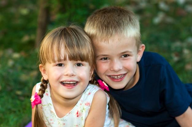 Portret dwojga dzieci chłopiec, dziewczyna brat i siostra siedzi wpólnie na trawie w parku