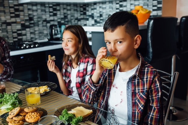 Portret dwojga dzieci siedzi i pije świeży sok i patrząc na kamery podczas relaksu