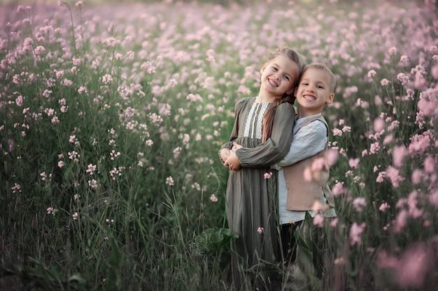 Portret dwojga ślicznych szczęśliwych dzieci. bliźniaki chłopiec i dziewczynka w lecie. na różowym polu kwitnienia.