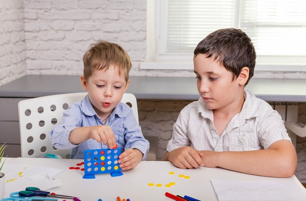 Portret dwojga wesołych dzieci są uśmiechnięte i grają razem w grę planszową na stole w domu.