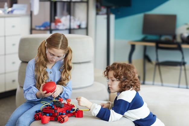Portret dwójki dzieci bawiących się maszyną robota podczas lekcji inżynierii w nowoczesnym wnętrzu szkoły, kopia przestrzeń
