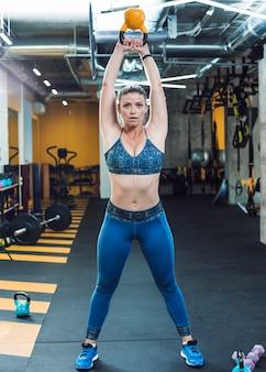 Portret dysponowana kobieta robi ćwiczeniu z czajnik piłką