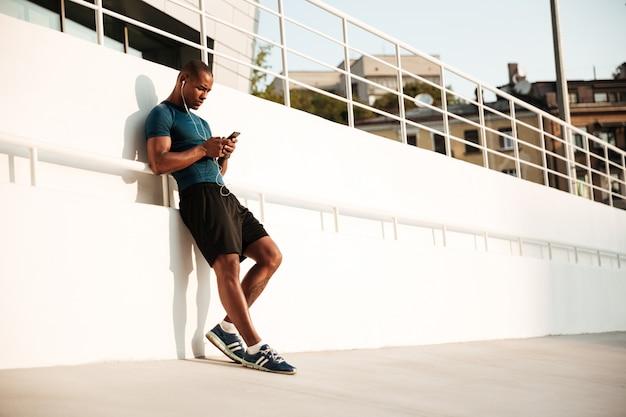 Portret dysponowanego afro amerykańskiego sportowa słucha muzyka