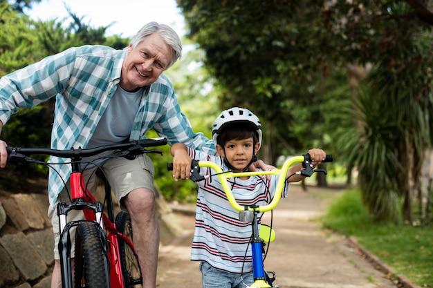 Portret dziadka i wnuka stojącego z rowerem w parku