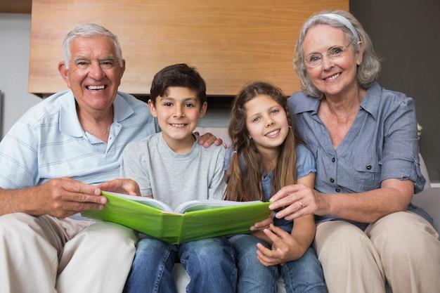 Portret dziadkowie i wnuki patrzeje albumową fotografię