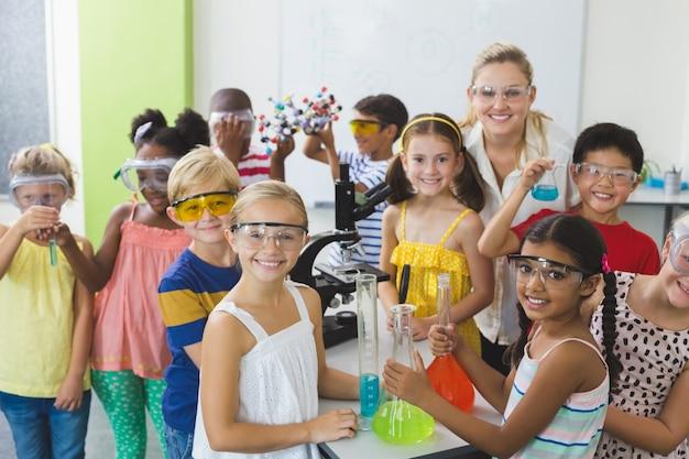 Portret dzieci i nauczyciel stoi w laboratorium
