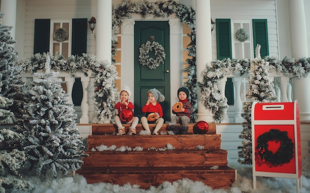 Portret dzieci siedzących razem na ganku swojego domu, jedz bułeczki. wesołych świąt szczęśliwego nowego roku. podwórko z choinką, światłami i dekoracjami. cudowny czas.