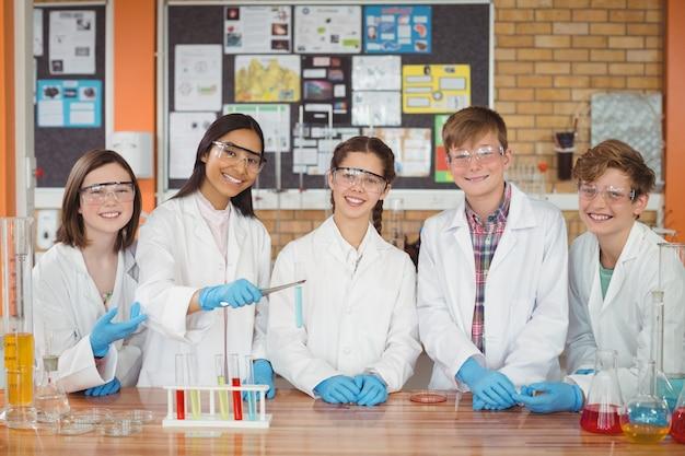 Portret dzieci w wieku szkolnym robi eksperyment chemiczny w laboratorium