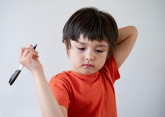 Portret dzieciak chłopiec trzyma pióro patrzeje w dół z zanudzającą twarzą.