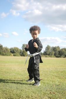 Portret dzieciaka ćwiczy karate w parku