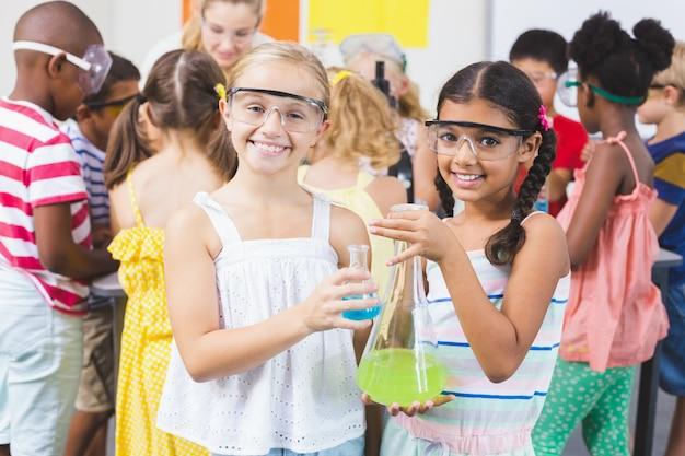 Portret dzieciaki trzyma laborancką kolbę w laboratorium