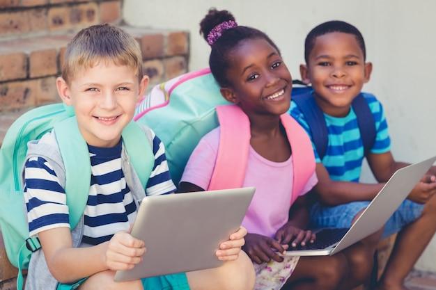 Portret dzieciaki używa laptop i cyfrową pastylkę na schodkach