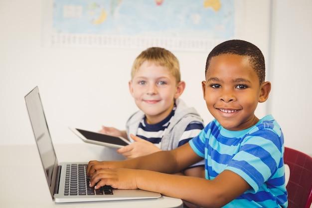 Portret dzieciaki używa laptop i cyfrową pastylkę w sala lekcyjnej