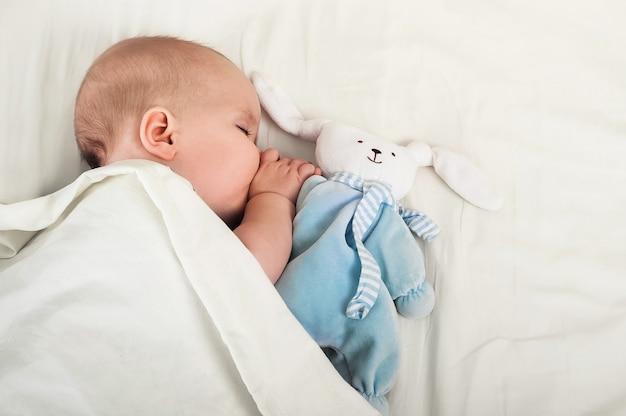 Portret dziecka 6 miesięcy śpi z zając zabawka. maluch, ząbkowanie, koncepcja snu dziecka.