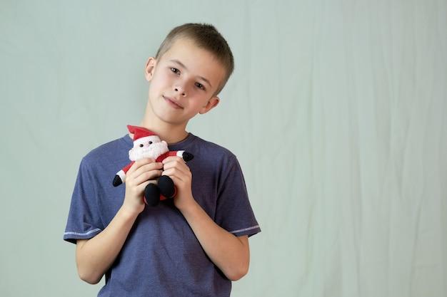 Portret dziecka bawiącego się małą zabawką mikołaja