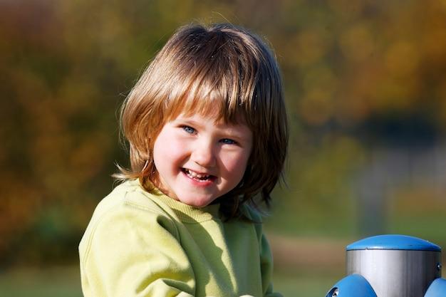 Portret dziecka bawić się na kolorowym boisku