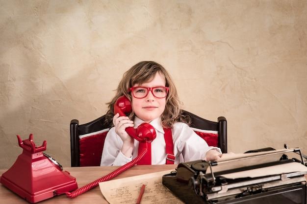 Portret dziecka biznesmen z retro telefonem. koncepcja komunikacji biznesowej