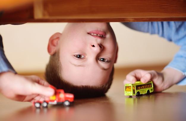 Portret dziecka chłopca w wieku przedszkolnym do góry nogami z samochodzikiem i autobusem w ręku. widok z podłogi spod łóżka.