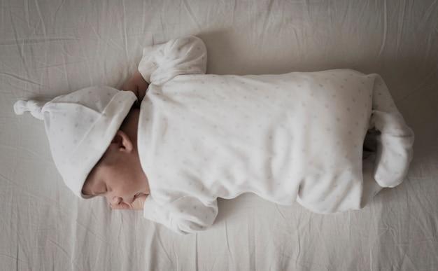 Portret dziecka dosypianie na białych prześcieradłach