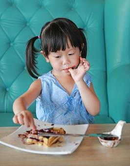 Portret dziecka dziewczyna je czekoladowych lody gofry jej palcem