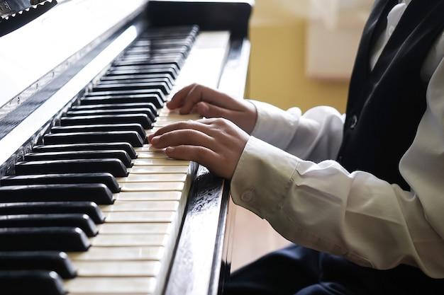 Portret dziecka grającego na pianinie, chłopiec uczący się muzyki z fortepianem w szkole muzycznej. dziecko relaksuje grając na pianinie