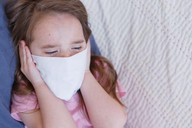 Portret dziecka, które zakryło twarz maską.