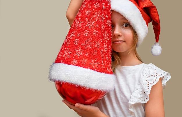Portret dziecka na czapce z ozdób choinkowych na czapce mikołaja.