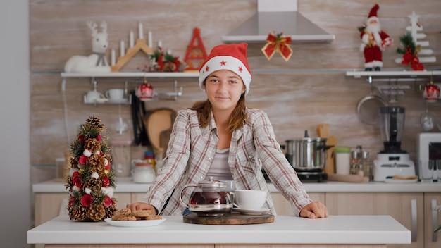 Portret dziecka patrzącego w kamerę stojącą przy stole z pieczonymi ciasteczkami i zaparzoną herbatą