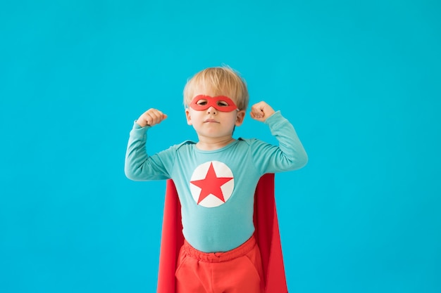 Portret dziecka superbohatera. dzieciak superbohatera na niebieskiej ścianie.