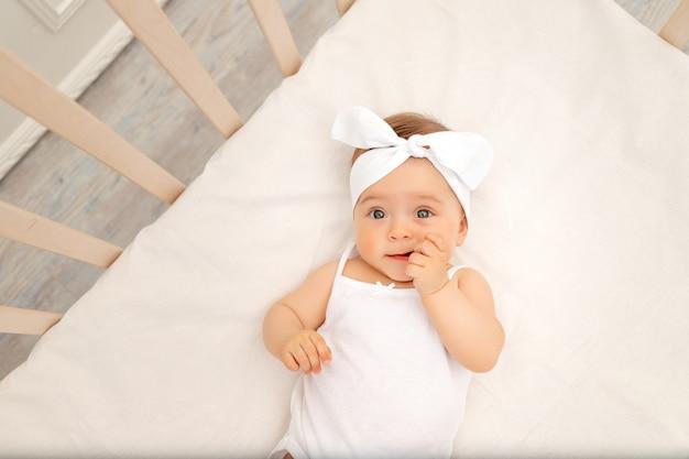 Portret dziecka w białym łóżeczku