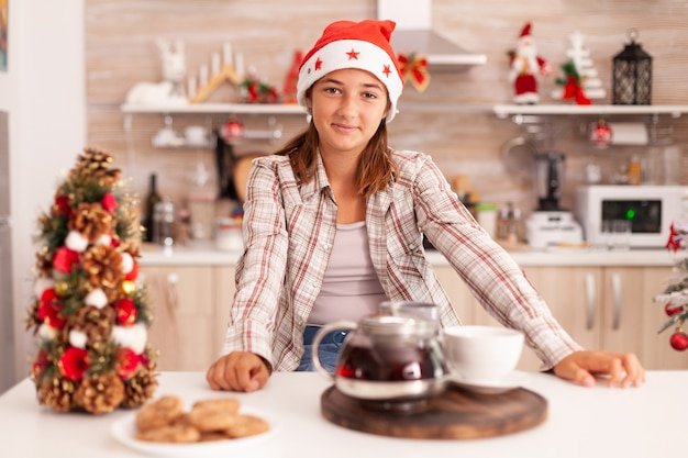 Portret dziecka w czapce mikołaja, patrząc w kamerę, ciesząc się sezonem zimowym