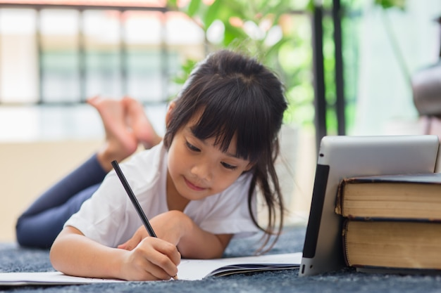 Portret dziecka w wieku przedszkolnym za pomocą tabletu do pracy domowej, nieostrość dziecka odrabiania lekcji za pomocą cyfrowego tabletu wyszukiwania informacji w internecie, e-learningu lub koncepcji edukacji domowej