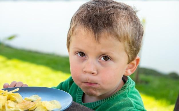 Portret dziecka w wieku trzech lat, jedzenie na świeżym powietrzu