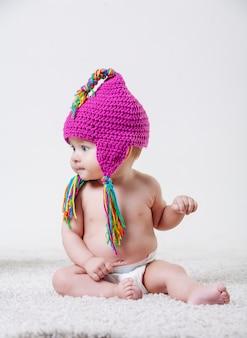 Portret dziecka z różowym wełnianym kapeluszem i kolorowymi frędzlami