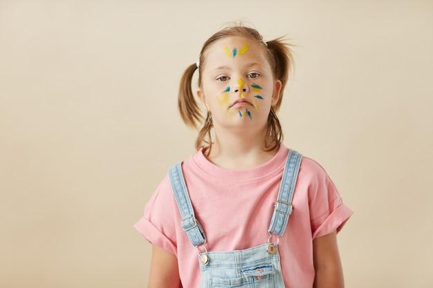 Portret dziecka z zespołem downa z pomalowaną twarzą na białym tle