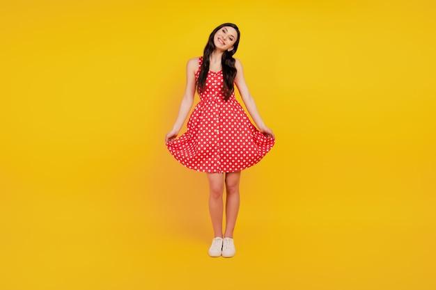Portret dziewczęcej uroczej damy pozującej w czerwonej sukience w kropki na żółtym tle
