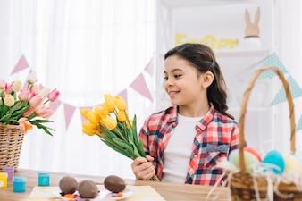 Portret dziewczyna patrzeje żółtych tulipanowych kwiaty na Easter dniu