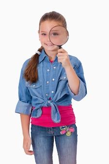 Portret dziewczyna patrzeje przez powiększać - szkło