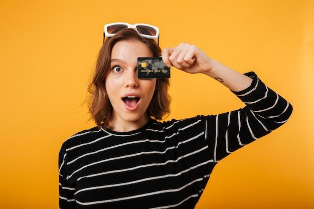 Portret dziewczyna trzyma kredytową kartę przy jej twarzą