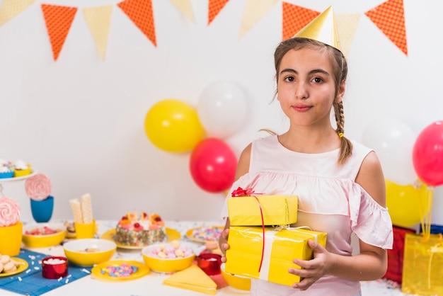 Portret dziewczyna trzyma prezenty urodzinowe w jej ręce
